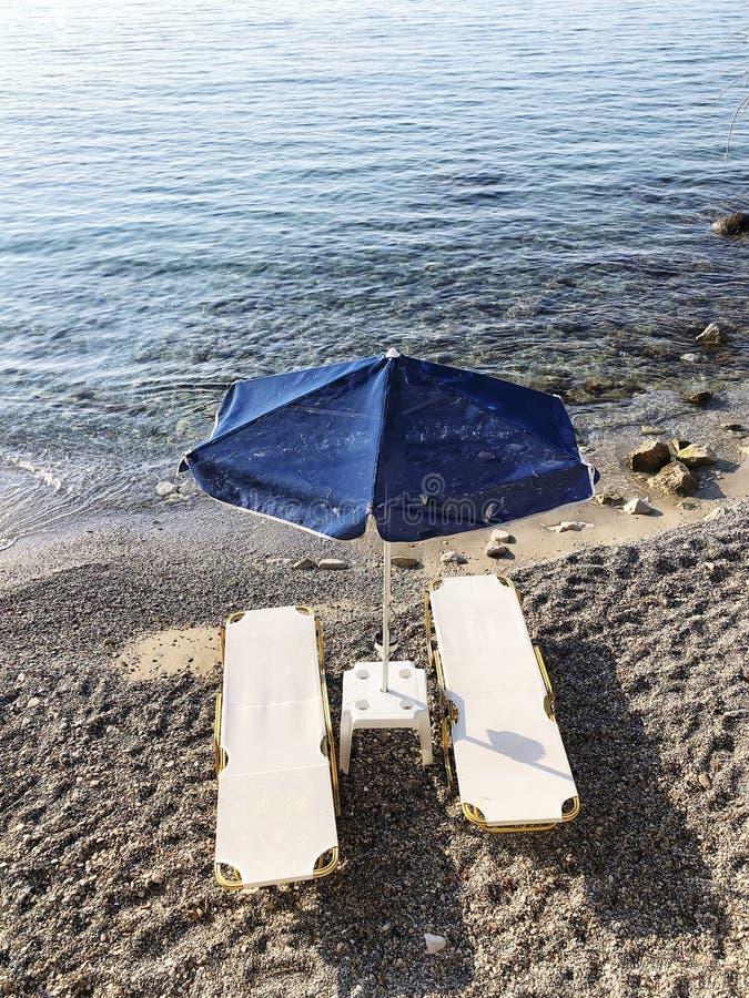 Puści sunbeds i parasol na piaskowatej plaży w lecie zdjęcie royalty free