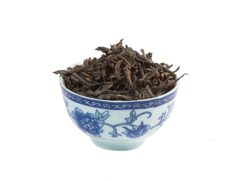 Pu-erh tea, loose leaf, isolated. Pu-erh tea in the Bowl, loose leaf, isolated stock photo