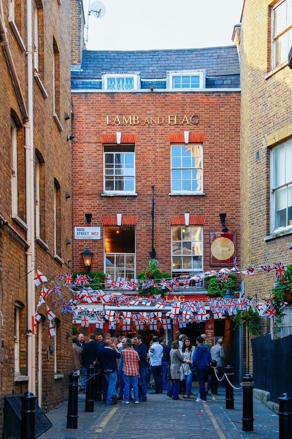 Pub con las banderas y gente local en calle en Londres foto de archivo libre de regalías