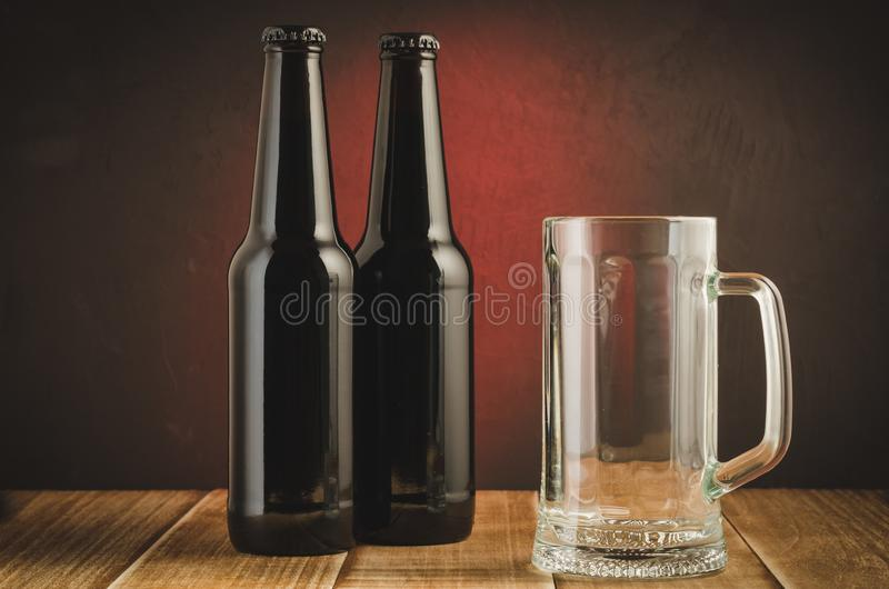 Pub with an empty glass and bottles of beer/pub with an empty glass and bottles of beer on a red background. Drunk three dark party bar gourmet drink beverage royalty free stock photography