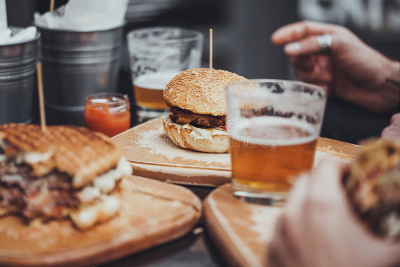 Pub Food. Delicious Pub Food. Burgers And Glasses Of Beer On Wooden Plates stock photo