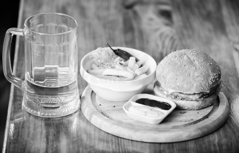 Pub food and mug of beer. Fast food concept. Burger menu. High calorie snack. Hamburger and french fries and tomato. Sauce on wooden board. Delicious burger stock photography