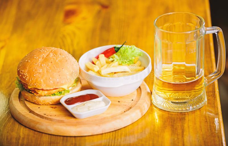 Pub food and mug of beer. Fast food concept. Burger menu. High calorie snack. Hamburger and french fries and tomato. Sauce on wooden board. Delicious burger royalty free stock photos