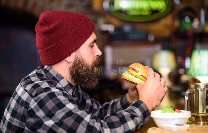 Pub jest relaksuj?cym miejscem mie? nap?j i relaksowa? M??czyzna z broda napoju piwem je hamburgeru menu Cieszy si? posi?ek w pub obraz royalty free