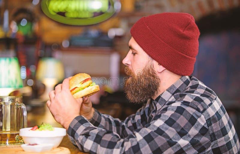 Pub jest relaksuj?cym miejscem mie? nap?j i relaksowa? M??czyzna z broda napoju piwem je hamburgeru menu Cieszy si? posi?ek w pub fotografia stock