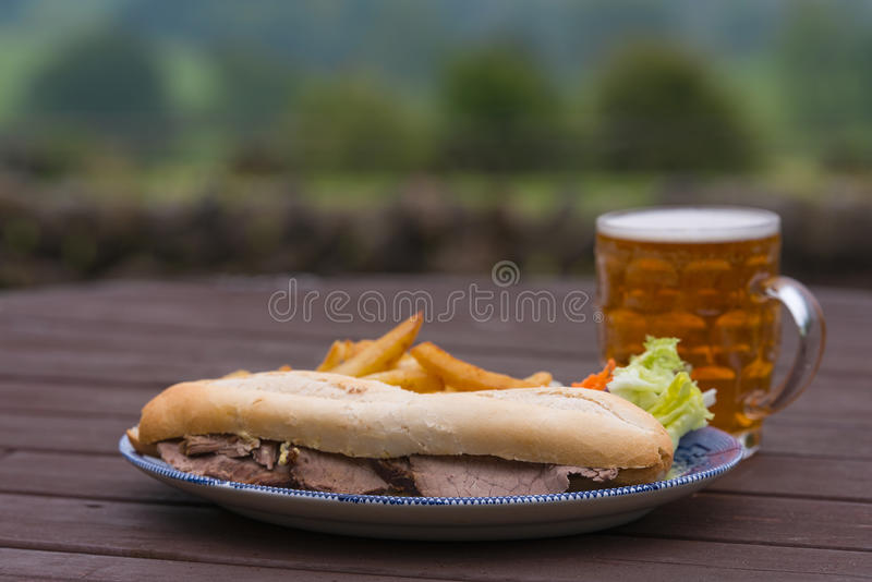 Pub lunch beef baguette. Hot beef baguette and pint of ale pub lunch at country pub stock photos