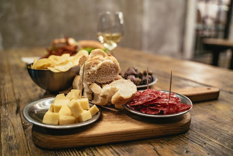 Pub lunch of cheese, spicy dried sausage and bread. Pub lunch of cheese, spicy dried sausage and crusty baguette bread served on a wooden board in a restaurant royalty free stock photo