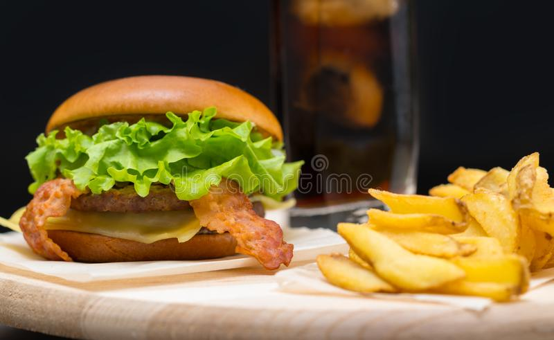 Pub lunch with a cheeseburger and french fries. Pub lunch with a tasty cheeseburger with bacon and lettuce served with crispy french fries and a cold soda stock images