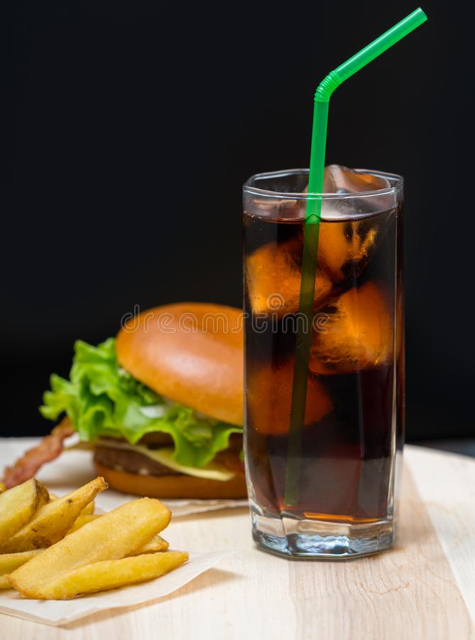 Pub lunch with cold coke, burger and French fires. Served on a rustic wooden board over a dark background with copy space stock photos