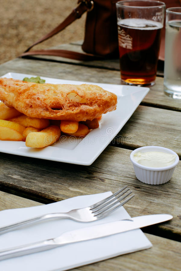 Pub Lunch. Fish and chips, traditional English dish, on an pub outdoor wooden table, beer on the background stock photos