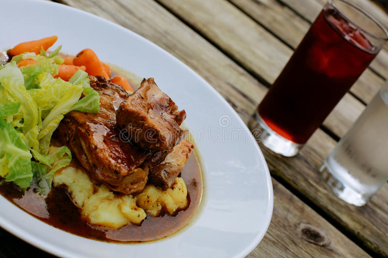 Pub Lunch. Lamb shank with vegetables on an pub outdoor wooden table royalty free stock photo