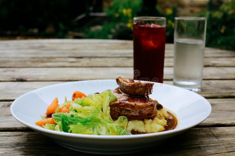 Pub Lunch. Lamb shank with vegetables on an pub outdoor wooden table, drinks next to it stock photography