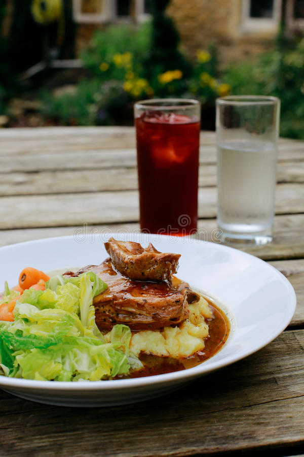 Pub Lunch. Lamb shank with vegetables on an pub outdoor wooden table, glass of water and juice next to it royalty free stock image