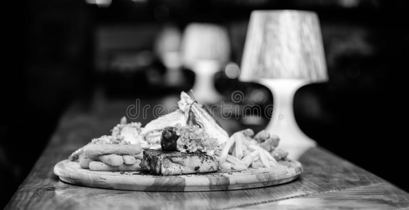 Pub menu snack. High calorie snack for group friends. Tasty delicious snacks. Snack for beer. Restaurant food. Wooden. Board with lot french fries fish sticks stock images