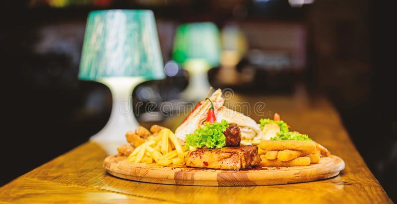 Pub menu snack. High calorie snack for group friends. Tasty delicious snacks. Snack for beer. Restaurant food. Wooden. Board with lot french fries fish sticks stock photos