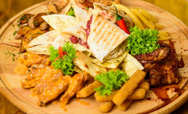 Pub menu snack. Meat snack for group friends. Tasty delicious snacks. Restaurant food. Snack for beer. Wooden board. French fries fish sticks burrito and meat royalty free stock images