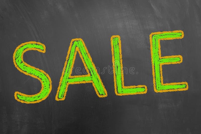 Pubblicità del testo del gesso di vendita sulla lavagna o sulla lavagna fotografia stock