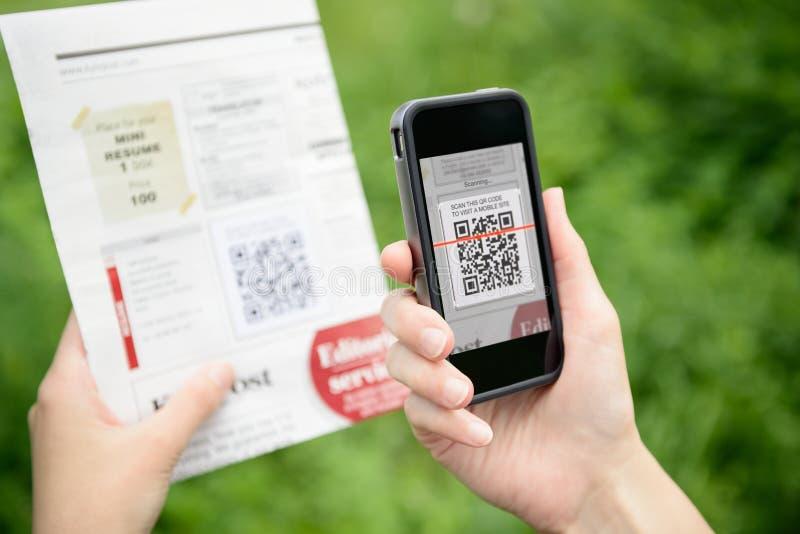 Pubblicità di scansione con il codice di QR su Apple Iphone fotografia stock libera da diritti