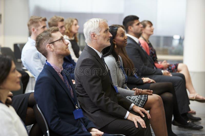 Pubblico che ascolta l'altoparlante alla presentazione di conferenza fotografia stock libera da diritti