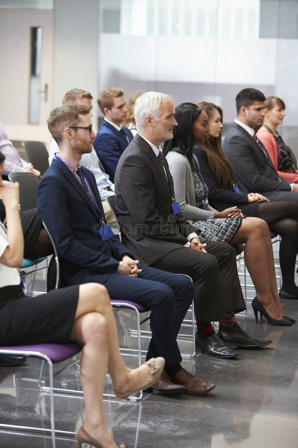 Pubblico che ascolta l'altoparlante alla presentazione di conferenza immagine stock libera da diritti