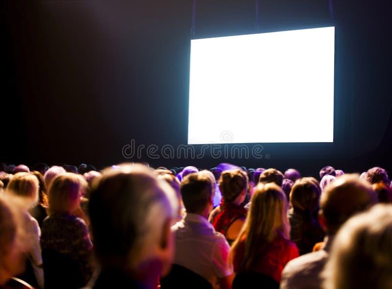 Pubblico della folla che esamina schermo fotografia stock libera da diritti