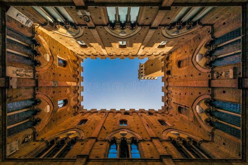 Pubblico do palazzo de Siena visto do interior contra o céu imagens de stock