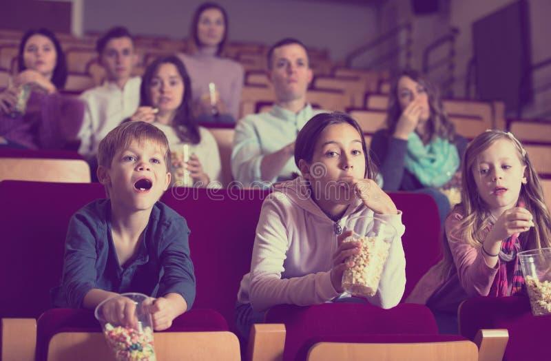 Pubblico entusiasta che assiste alla notte di film con popcorn immagine stock