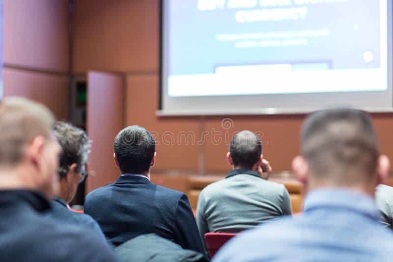 Pubblico nella sala per conferenze che ascolta la presentazione sull'incontro di affari fotografia stock