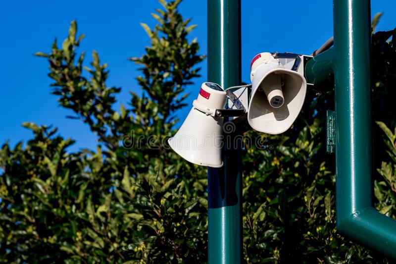 Public address bullhorn outdoor speakers on a green. Post in front of trees royalty free stock photography