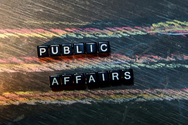 Public Affairs on wooden blocks. Cross processed image with blackboard background. royalty free stock photos