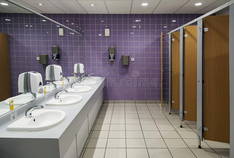 Public Bathroom. With mirrors, cubicles and sink units stock photo