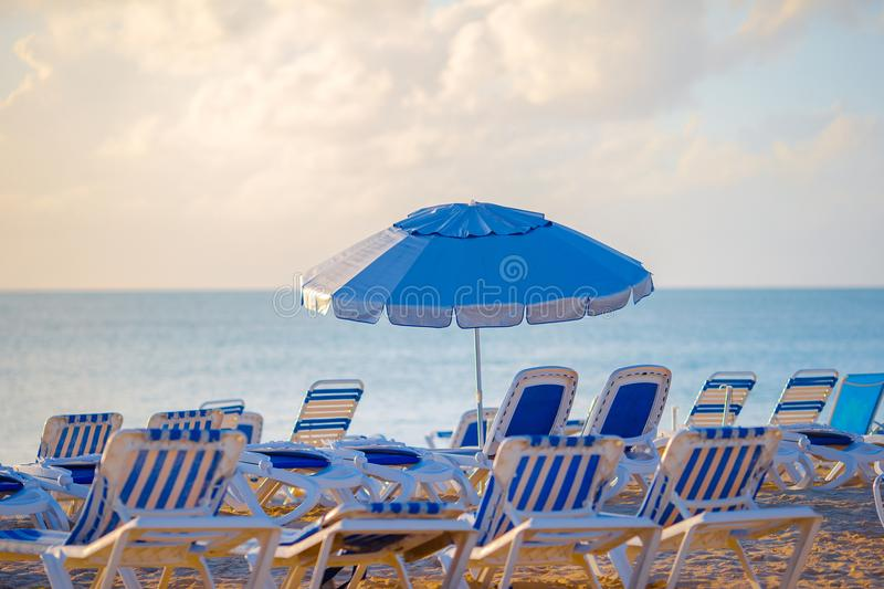Public beach in a popular resort in the Caribbean with umbrellas and chaise-lounges stock image