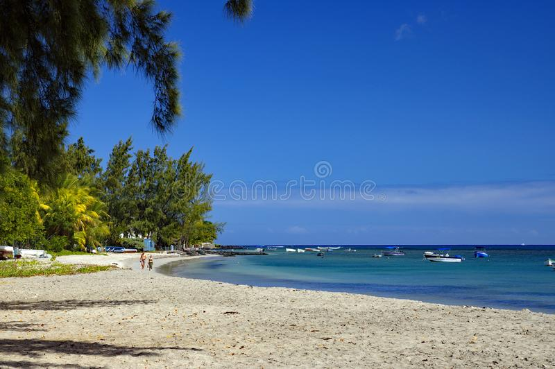 The public beach of Tamarin beach, Black River District, Mauritius Island. TAMARIN/MAURITIUS - AUGUST 20, 2018: People in a sunny day walking on the public beach stock image
