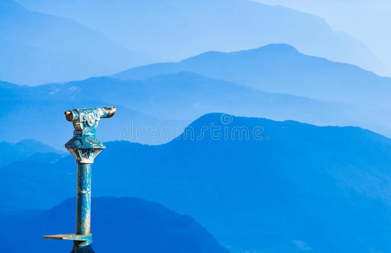 Public binoculars. Foresight and vision for business concept and ideas. Public binoculars provide far view to distant blue mountain ranges. Foresight and vision royalty free stock photo