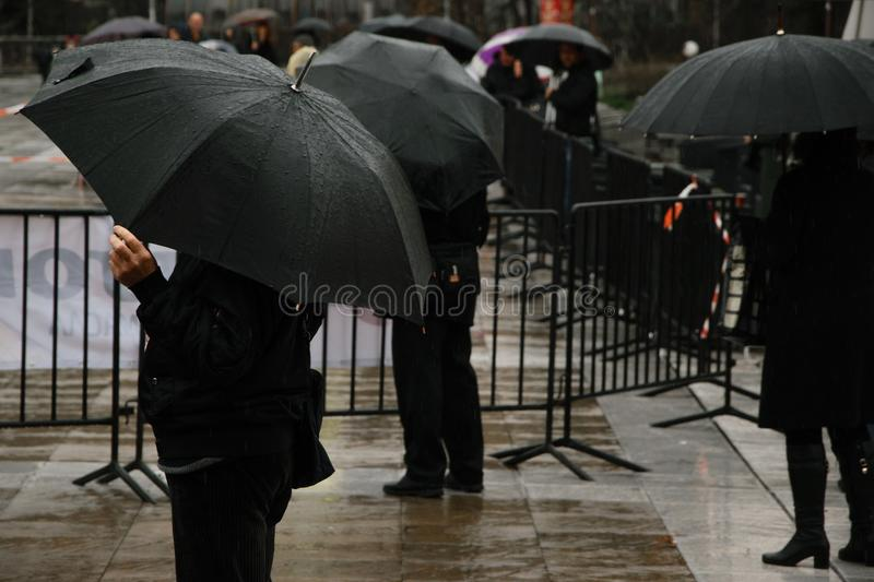 Public in black waiting/watching of a city event in the rain. Blagoevgrad stock photos