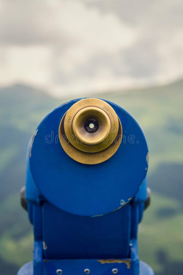 Public telescope arrayed against mountain range Alps in Austria, cloudy summer day. Public blue telescope arrayed against mountain range in Alps, Austria, cloudy stock image