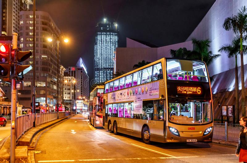 Public bus services in Hong Kong are popular with tourists. Night cityscape with city buses by HK Cultural Centre and Star Ferry. Hong Kong - January 12, 2016 stock image