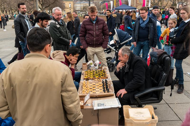 Public chess game by amateurs on the central historical street of Koenigstrasse King Street. STUTTGART, GERMANY - MARCH 04, 2017: Public chess game by amateurs stock images
