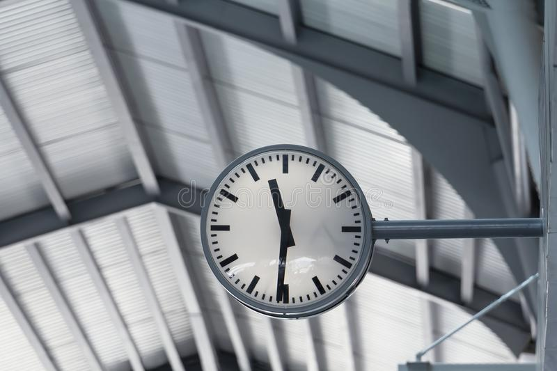 Public clock in railway station at the hanging with roof of subway central train station. It is clock for watch time waiting train stock image