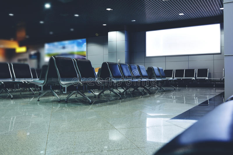 Public commercial board in waiting of airport hall with empty chairs royalty free stock photography