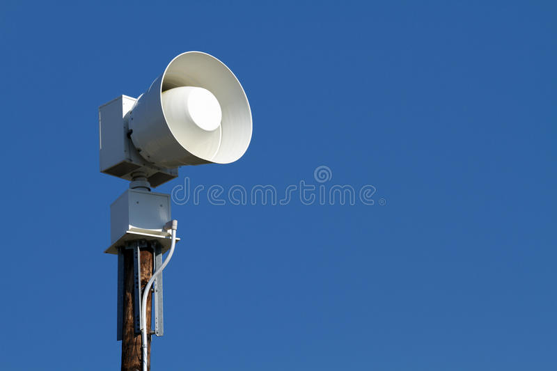 Public Emergency Warning Siren. A modern public emergency warning siren horn on a wooden pole against a clear blue sky. These are used for local community stock photo