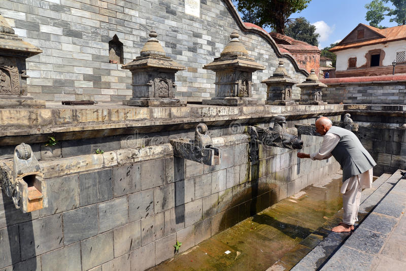 Public fountain in Pashupatinath, Nepal. PASHUPATINATH - OCTOBER 8: An unidentified old man drinking water from a public fountain during the Dashain festival. On stock images