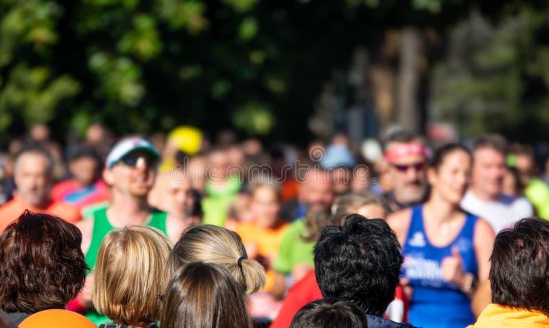Public heads contemplate city marathon runners stock photos