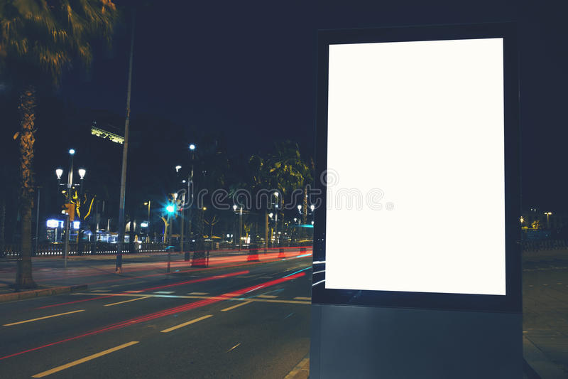 Public information board in night city with beautiful dusk on background. Illuminated blank billboard with copy space for your text message or content, public stock photo