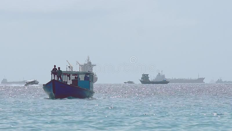 Public Maldivian Ferry Workers. Empty Public Transport Ferry Called Dhoni, Arriving At The Harbor Of Malé International Airport With Two Workers Standing In royalty free stock photography