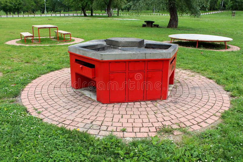 Public park with multiple open concrete and metal barbecues for public use surrounded with stone tiles next to benches and royalty free stock images
