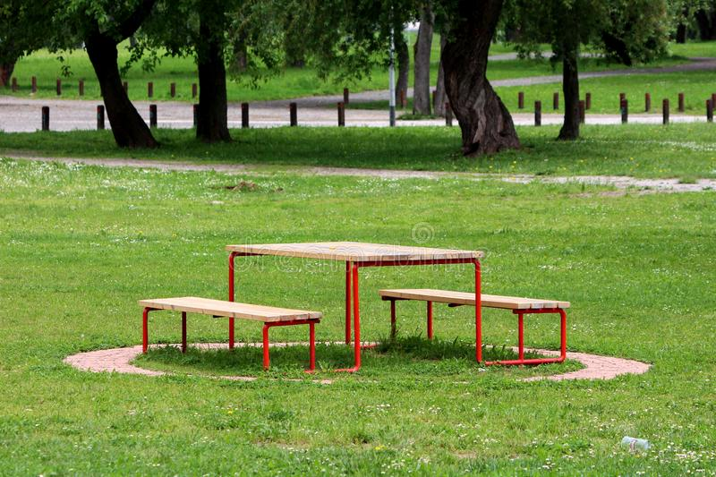 Public park wooden table with benches supported with metal frame surrounded with stone tiles uncut grass and trees in background royalty free stock photo