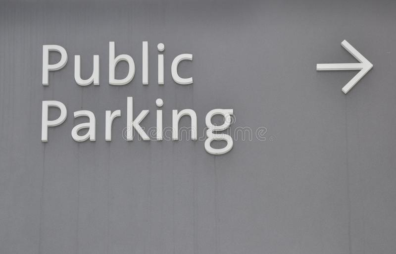 Public parking. With arrow sign attached to the wall stock image