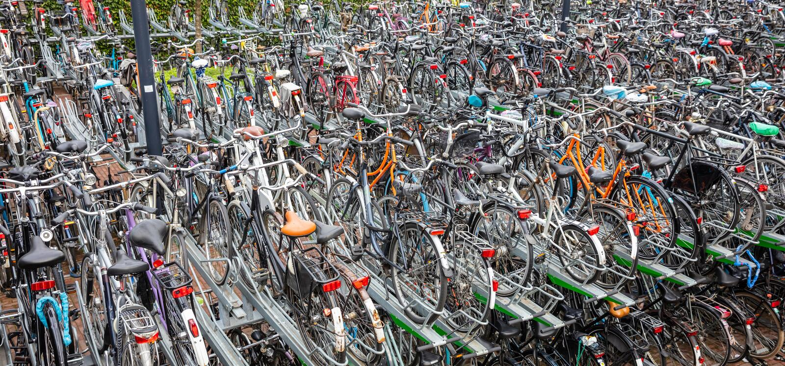 Public parking lot for bicycles in Rotterdam, banner, background. Colorful bicycles in a public two-storey parking station, in the city center of Rotterdam stock images