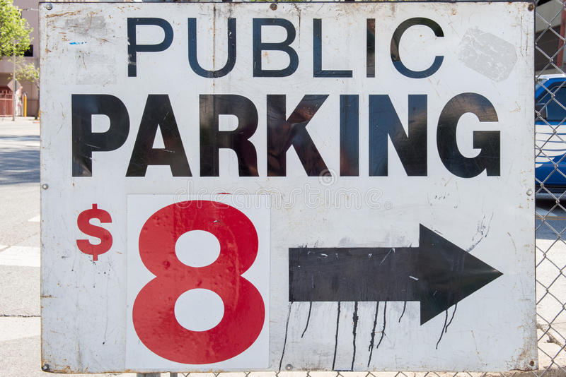Public Parking Sign. Advertising an $8 fee, tied to a chain link fence stock photo